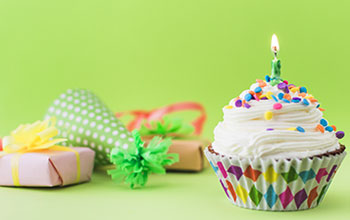 Cupcake with 1 candle, wrapped present, and a party hat all on a green table with a green background.